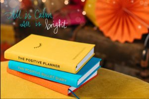 The 3 books for The Positive Bundle - The yellow Positive Planner, The orange Positive Wellness Journal and the blue Positive Bullet Diary lie stacked surrounded by festive Christmas decorations