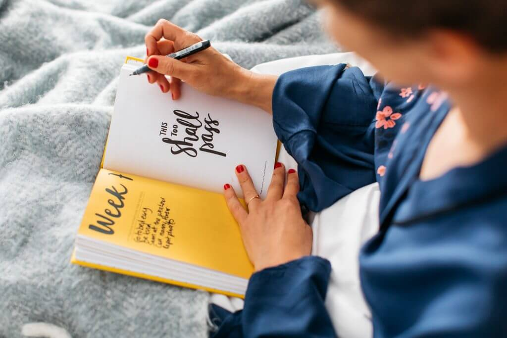 A lady in a blue dressing gown sitting in bed with an open Positive Planner journaling