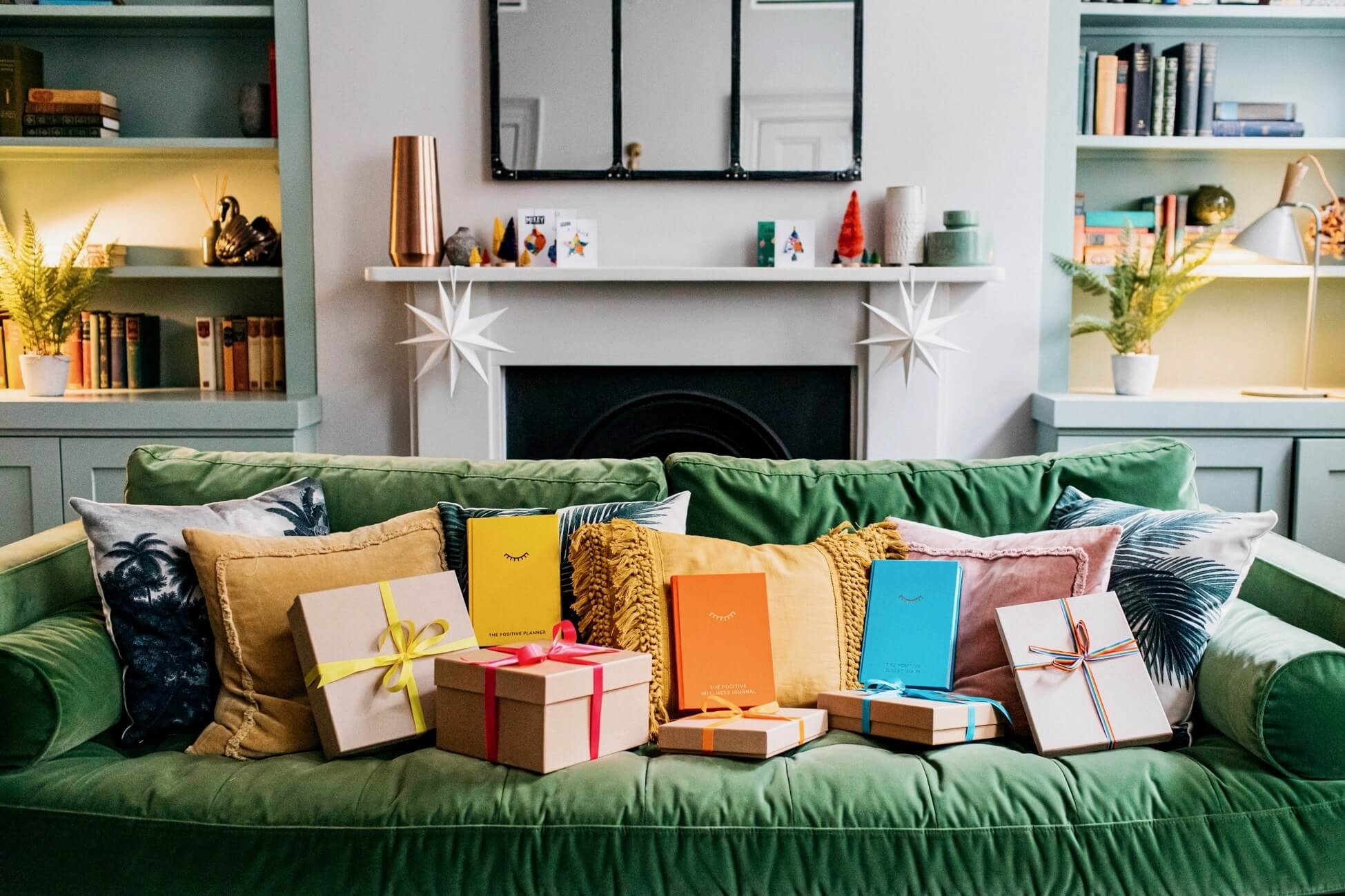 A green sofa covered in the gifts available in The Positive Planner self-care gift guide