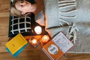 The Positive Wellness Journal being used as a meditation guide by a lady lying on a yoga mat surrounded by The Positive Planner and The Positive Bullet Journal books and relaxing candles. A good way to combat mental fatigue in lockdown