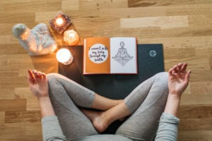 The Positive Wellness Journal open showing detail of positive affirmations next to lady seated meditating