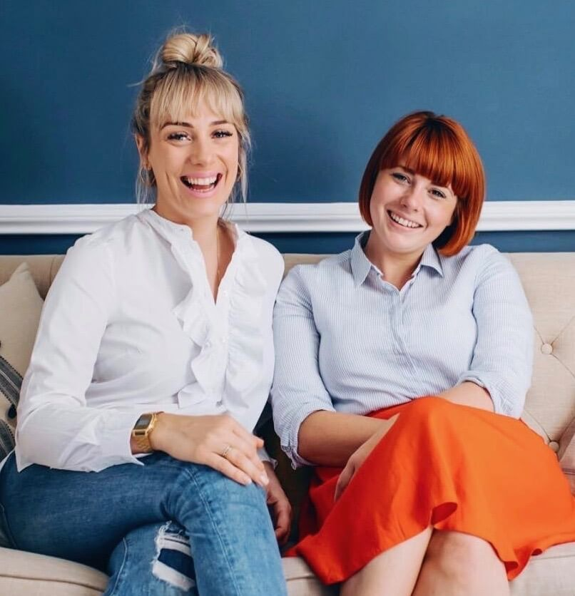 Co-founders of The Positive Planner Ali + Finn sitting on a sofa together