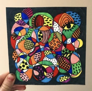 A child hold the Braintangle they have created and coloured in with vivid colours and patterns