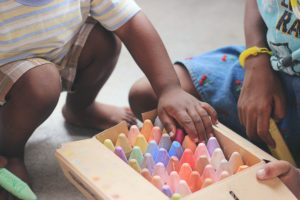 2 small children of colour with a box of large chalk crayons