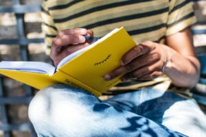 A man writing in the yellow, hard-backed book The Positive Planner