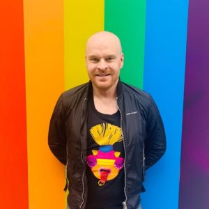 HIV and Mental Health Activist Philip Baldwin stands in front of the LGBTQ flag. He talks about HIV and Mental Health in this guest blog