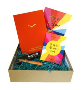 The Positive Affirmation Box showing its contents The orange Positive Planner, a vibrant box of Positive Affirmation Cards, a Kaweco fountain pen in orange and a Positive Planner Christmas Card