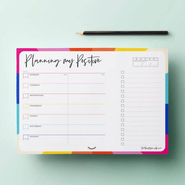Image of The Positive Week Desk Pad Planner with a pencil