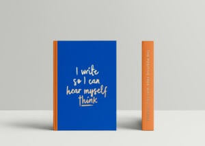 The Positive Free Writing Journal showing its bright orange fabric spine and vivid blue cover with the embossed message I Write So I can Hear Myself Think recommended in our Positive Self-Care Gift Guide