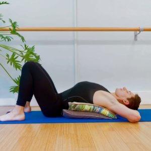Yoga teacher James Downs demonstrates the restorative yoga pose Heart opener over cushions