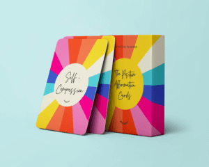A rainbow-coloured pack of Positive Affirmation Cards with 2 affirmation cards leaning against the storage box. Part of the Positive Planner Self-Care Gift Guide for Christmas 2020