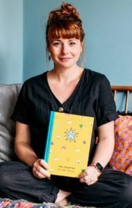 Co-founder of The Positive Planner Ali McDowall sat holding The Positive Doodle Diary - the perfect book to help you journal with children