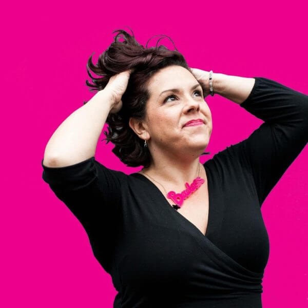 Portrait of Life Coach and NLP Practitioner Mary Meadows wearing a black top against a bright pink background
