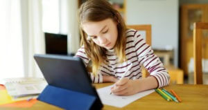 A young girl sat at a desk with a computer tablet. Creating a workspace with your child is an important process in learning how to homeschool