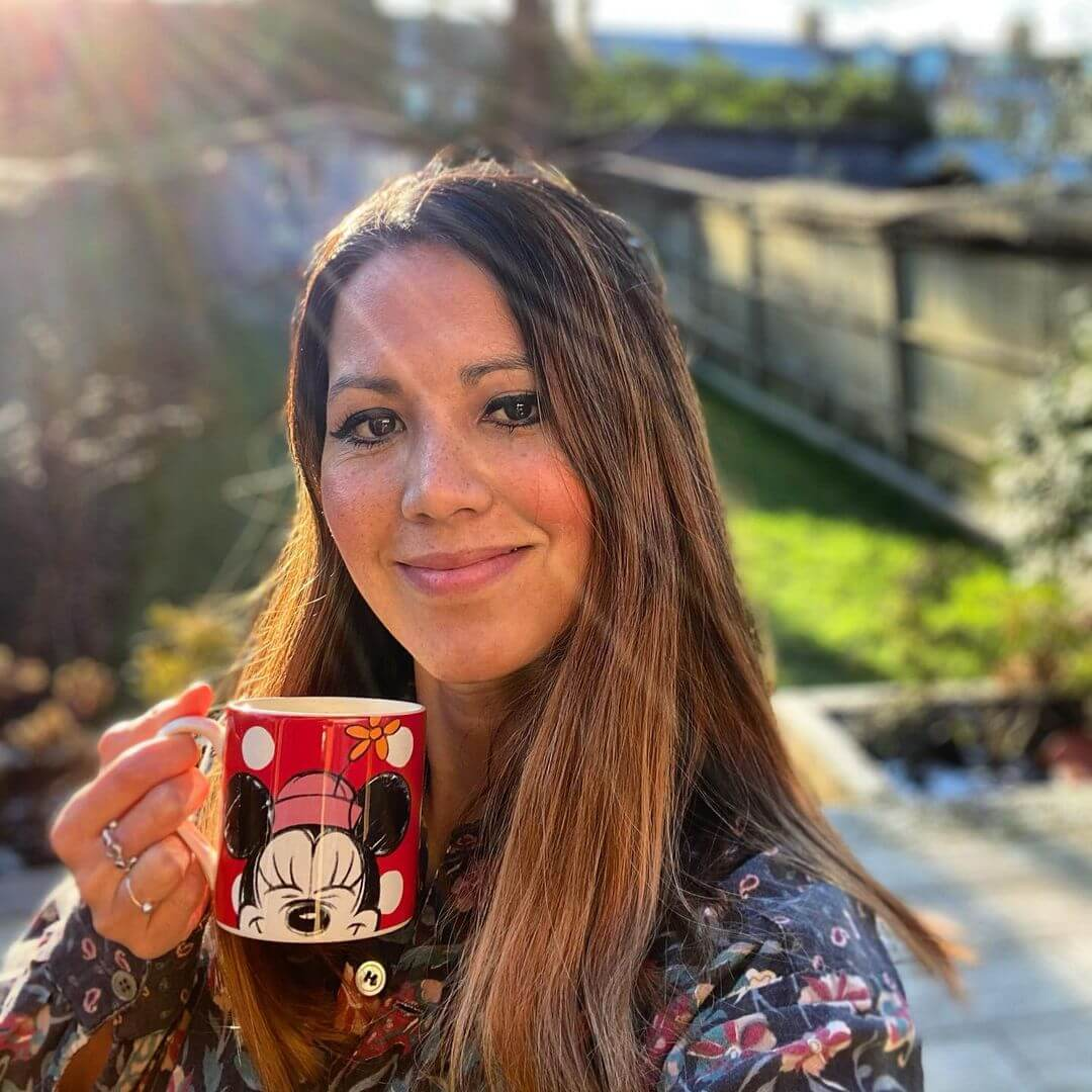 Dr Martha Deiros Collado holding a mug with Minnie Mouse on it in her garden. Her guest blog gives her expert answers on tweens and teens mental health.