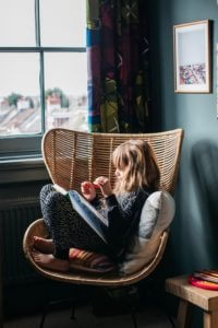 A little white girl colouring in a book sitting in a chair next to a window. Colouring is an excellent self-soothing exercise that we can use to help children learn about their emotions