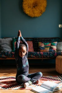 A little black girl sitting in a yoga pose on a patterned rug in a brightly coloured room Yoga is an excellent self-soothing exercise that we can use to help children learn about their emotions