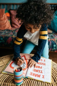 A little black boy colouring in a book in a brightly coloured room. Colouring is an excellent self-soothing exercise that we can use to help children learn about their emotions