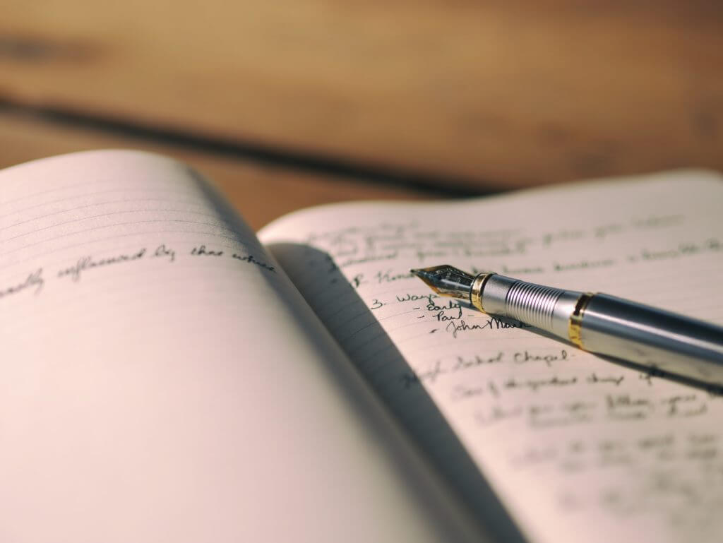 A journal laid open showing slightly out of focus writing together with a fountain pen. For people who can't journal, a blank page can be daunting