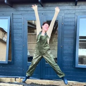 The Positive Planner Ali McDowall wearing green work dungarees doing a star jump in front of a dark blue garden cabin