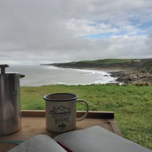 An open journal with a cup of coffee looking out onto a coastline