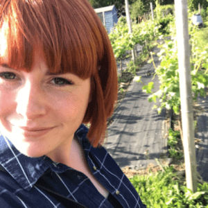 The Positive Planner co-founder Ali McDowall wearing a dark blue checked shirt standing in front of her gardening allotment