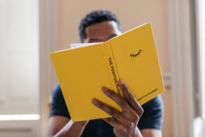 A Black man in a dark blue t-shirt holding an open copy of The Positive Planner