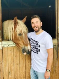 co-founder of youth mental health charity Jonny Benjamin standing next to a horse in a stable